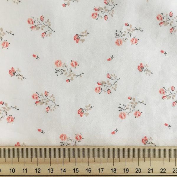 détail du tissu imprimé fleuri avec des petites roses et feillages beige tissu fleuri fond blanc lait